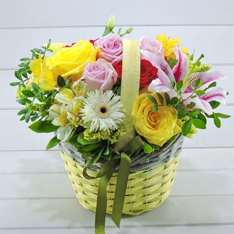 Ανοιξιάτικη σύνθεση με λουλούδια σε ξύλινο καλαθάκι