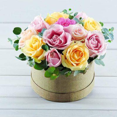 χρωματιστά τριαντάφυλλα σε χάρτινη καπελιέρα